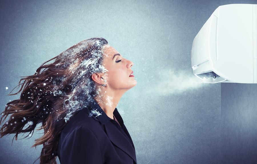 Frozen girl under a powerful air conditioner